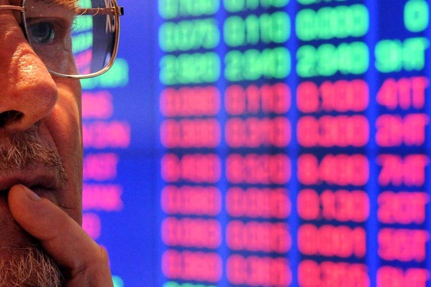 Investor at ASX watches stock price monitors (AFP: Torsten Blackwood)