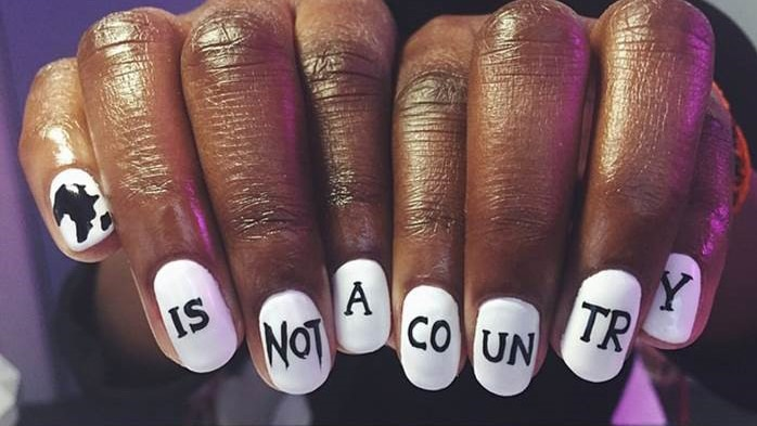 Hands showing white nails with black text saying: Africa is not a country