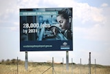 "A sign by the road says ""28,000 jobs by 2031"""