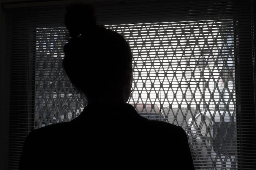 A silhouette of a woman as she looks out of a window