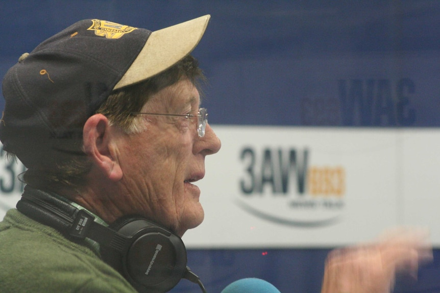 A man wears a baseball cap and headphones in a radio studio with a '3AW' banner in the background.