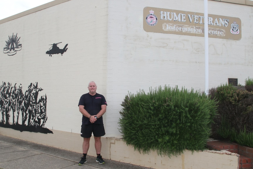 Hume Veterans' Information Centre Secretary Jason Sofield stands in front of the aging beige Wodonga building they're based in.