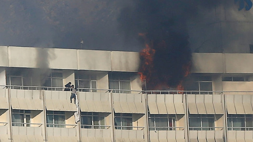 Black smoke and flames spew out of a top floor room while a man hangs off a nearby balcony clinging to bedsheets.