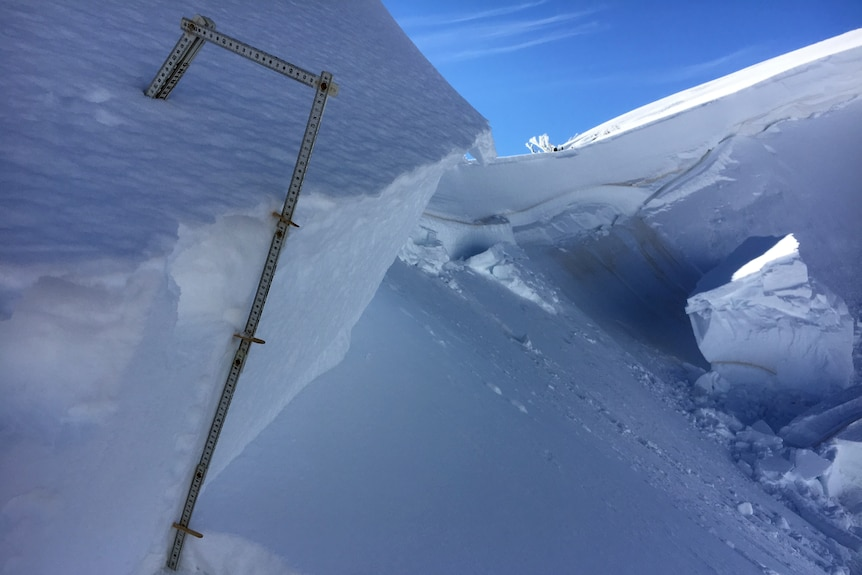 A stick measures the amount of snow that collapsed from a ledge.