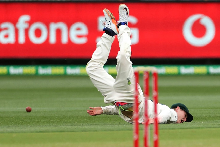 An Australian Test cricketer falls face first into the turf as the ball runs away in the background.