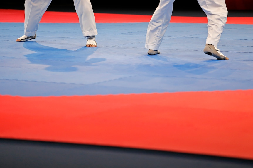 An image of the feet of two athletes competing on the mat in a taekwondo tournament