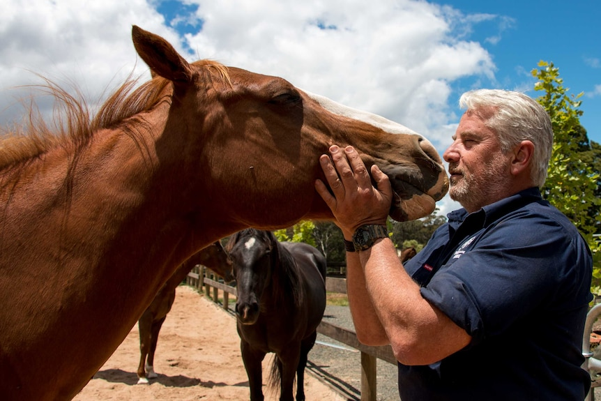 Dean Mighell kisses one of his horses on his property at Trentham, in Central Victoria.