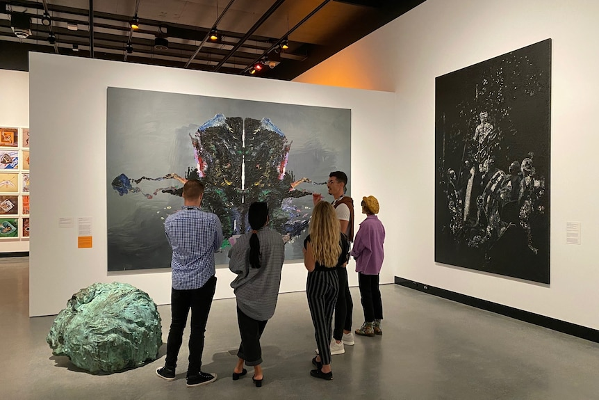 Five people stand with their backs to the camera looking at a large painting which is styled like psychologist's Rorschach test