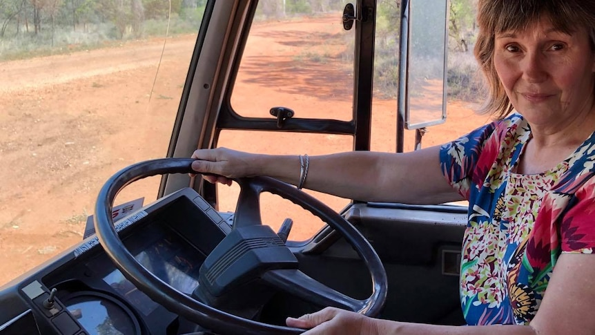 A woman sits behind the wheel of a truck on a dirt road