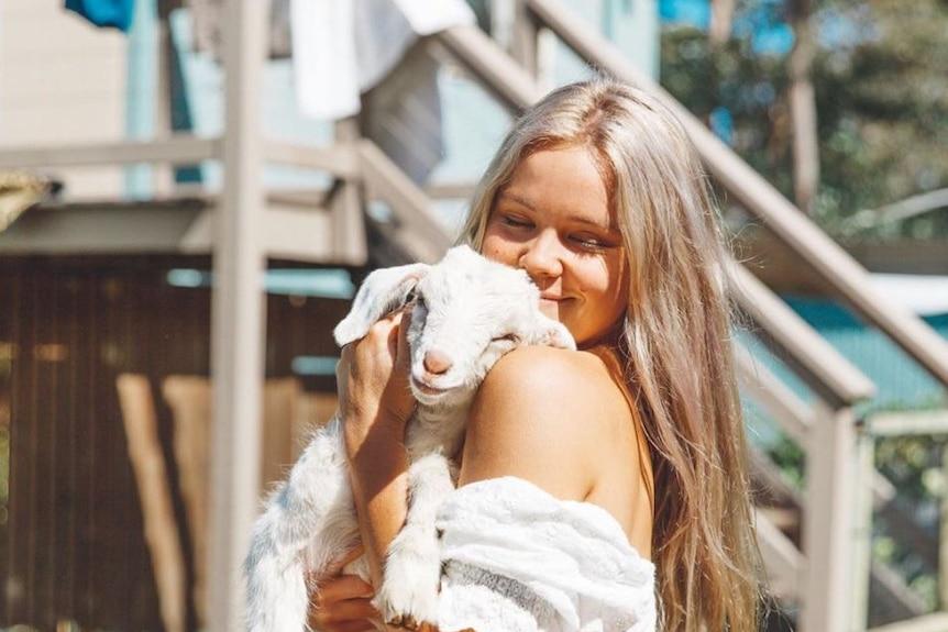 Lauren McGeachin cuddles a goat.