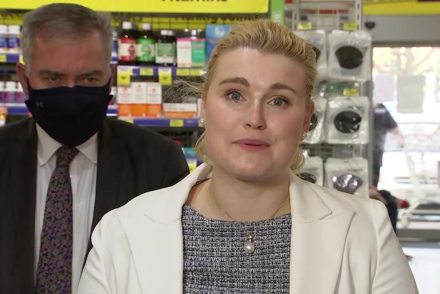 A blonde woman wearing a white jacket
