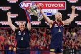 Simon Goodwin and Max Gawn hold the AFL trophy above their heads