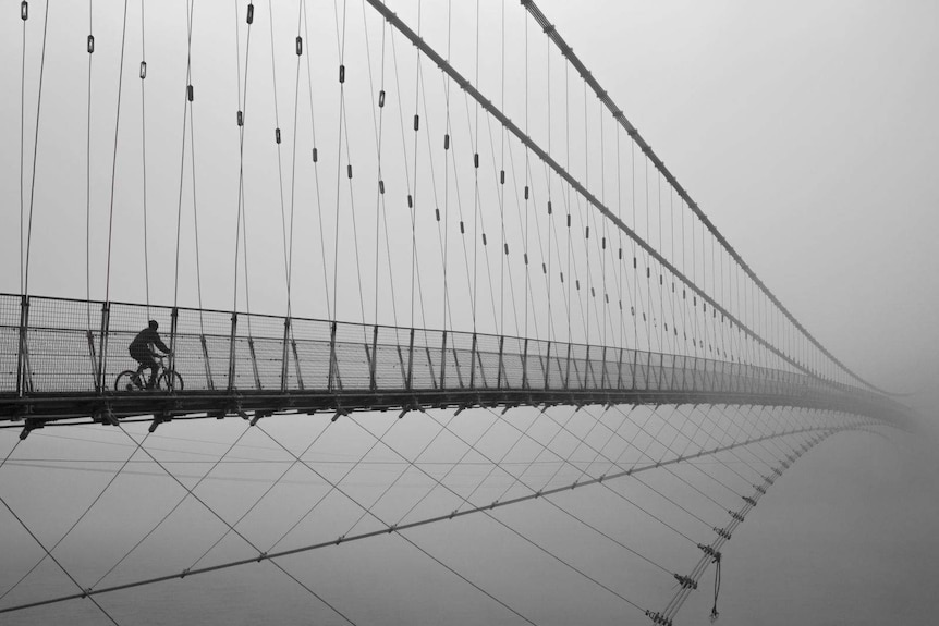 A traveller is seen riding across Ram Jhula bridge in India.