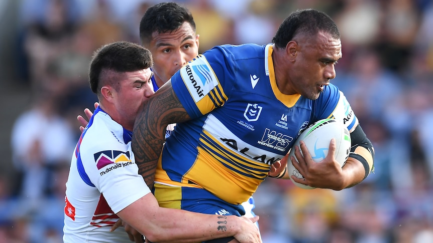 A Parramatta Eels NRL player holds the ball with his right hand as he is tackled by two Newcastle Knights opponent.