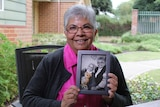 Deidre de Souza sits on a chair outside smiling and holding a black and white photo of her with her mum.
