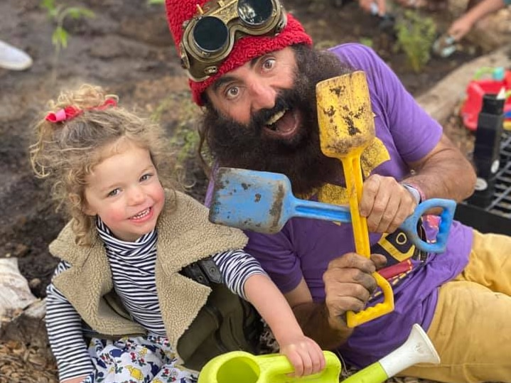 A young girl sits in the dirt next to a man with a huge beard in fancy dress holding two coloured mini shovels.