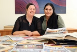 Koori Mail editor Rudi Maxwell and general manager Naomi Moran with past editions of the newspaper