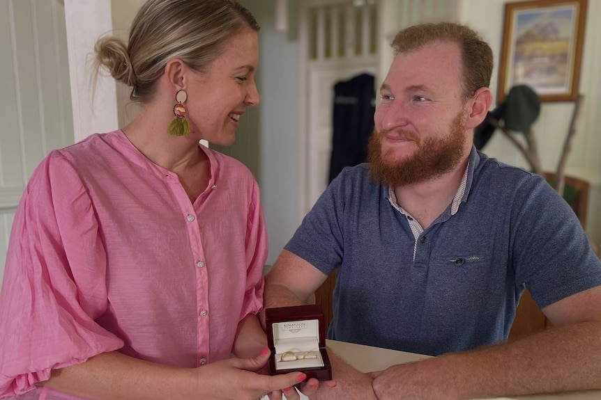 A man and a woman look into each other's eye as they hold a wedding ring