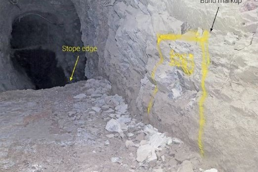 A photograph inside an underground gold mine with markings showing the edge of an open void known as a stope.