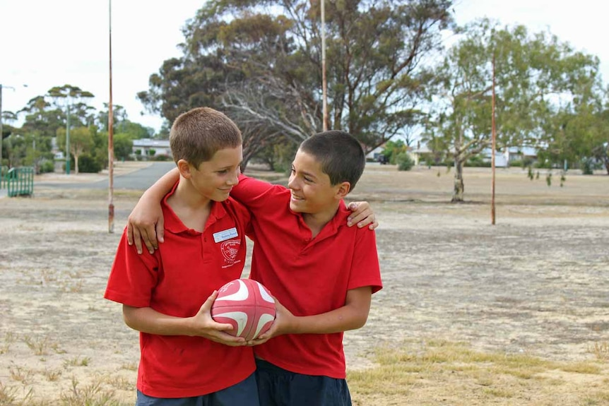 Two boys play with a football in front of old goalposts on a dirt oval.