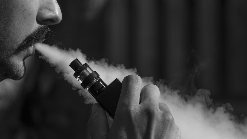 Man's face half hidden, blowing smoke out of mouth from e-cigarette that he's holding in his hand.