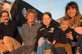 Four people and a baby sit on a yacht.