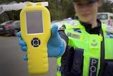 Female Tasmania Police officer with breathalyser at random testing station