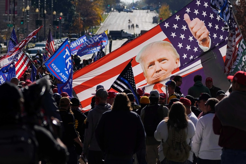 Supporters of President Donald Trump hold a banner with Trump's picture in front of a US flag.