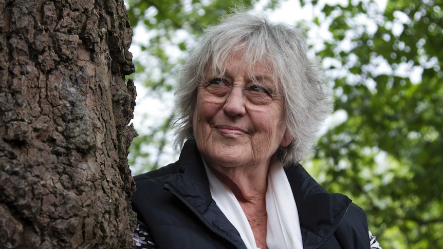 Legendary Australian feminist writer Germaine Greer, standing next to a tree, smiles as she looks up into the sky.