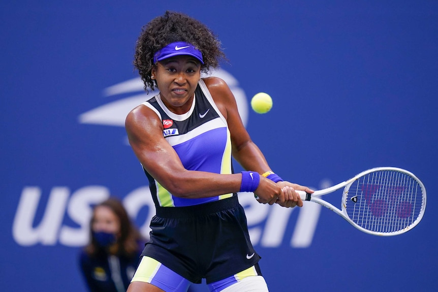 A tennis player eyes the ball as she brings the racquet back to hit a backhand at the US Open.