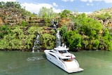 A super yacht sits beneath a waterfall