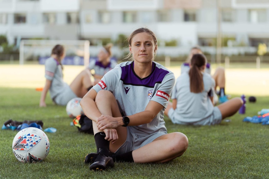 A woman wearing a sports jersey sits on a sports field with a soccer ball next to her