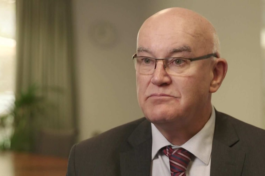 John Skerritt in his office wearing glasses, a black suit and a maroon tie