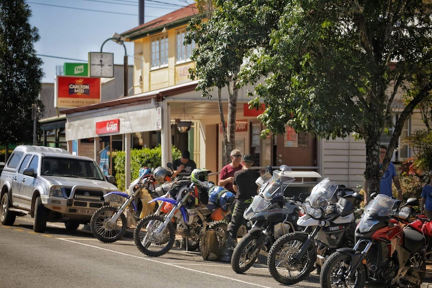 A row of motorcycles parked outside a country convenience store