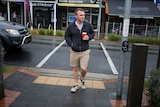 Chris May crosses the street holding a coffee cup