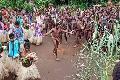 A man wearing no clothes except for a covering around his waist dances in the middle of a group of men and women.
