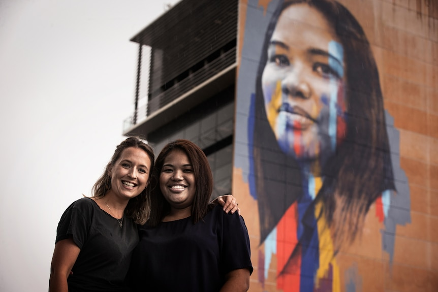Two women stand together underneath a large mural of one of their faces on the side of a building.