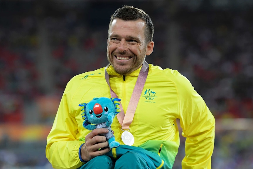 Kurt Fearnley smiles with a silver medal around his neck and a Commonwealth Games mascot in his hand.