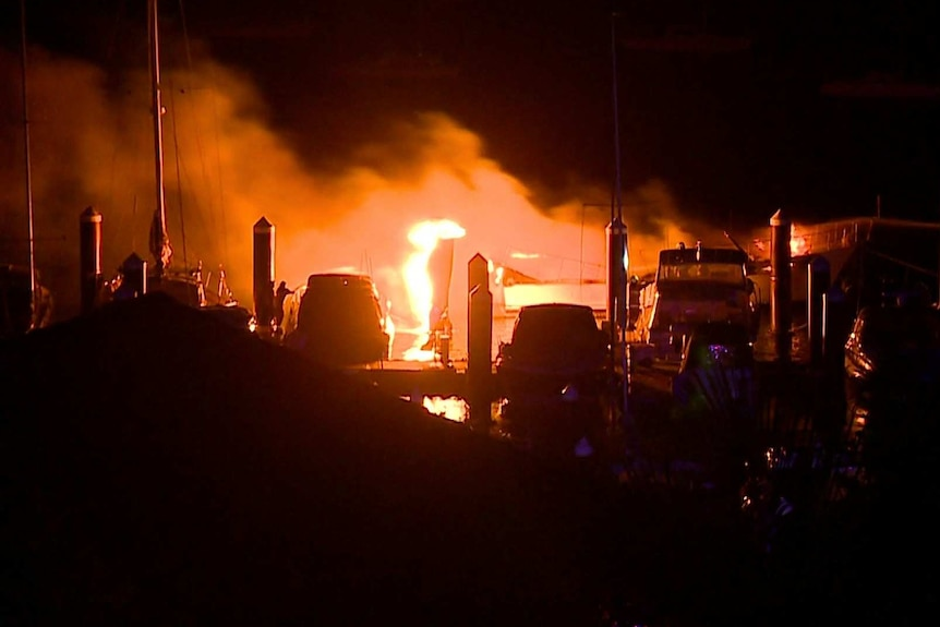 Firefighters hold hoses towards a boat which is well alight on a marina.