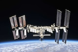 The International Space Station in orbit above the Earth, with solar panels unfurled, as seen from another craft