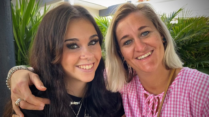 Teenage daughter with long, dark hair sits closely with mum who has blonde hair, both smiling.