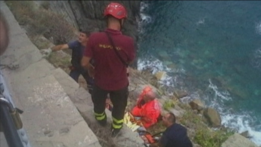 One of the trapped Australians is pulled to safety