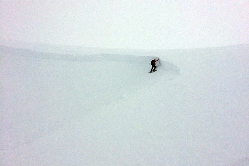 A skier is seen standing on the side of a mountain covered in snow.