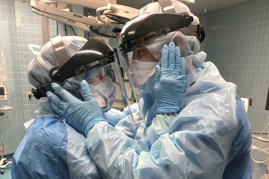 A man and a woman in full protective gear clutch each others faces