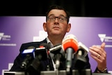 Daniel Andrews speaks to media at a press conferences with microphones in front of him