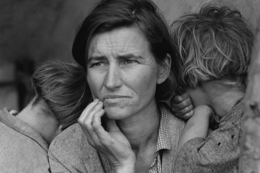 An old black and white photo of a mother during the Great Depression holding her children