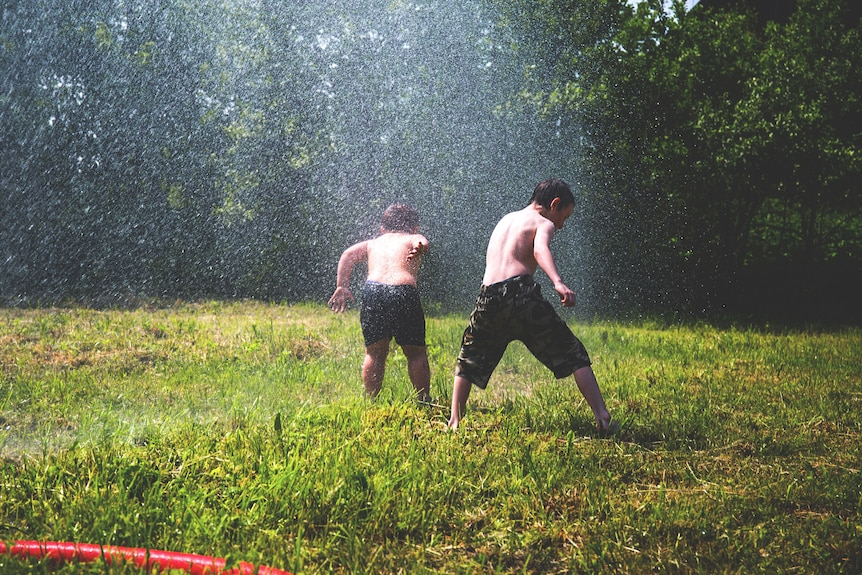 Two children playing with a sprinkler
