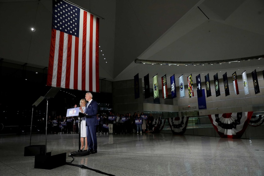 Joe Biden and his wife Jill stand at a podium in a large room with a long American flag hanging above them.