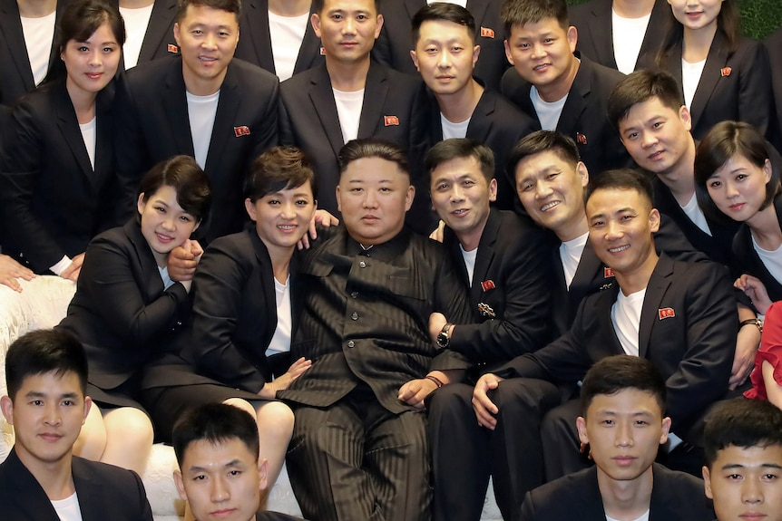 Kim Jong Un on a couch surrounded by people in dark suits and white t-shirts