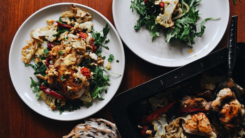 Two plates of rocket topped with baked chicken, capsicum and cauliflower, a healthy family tray bake recipe.
